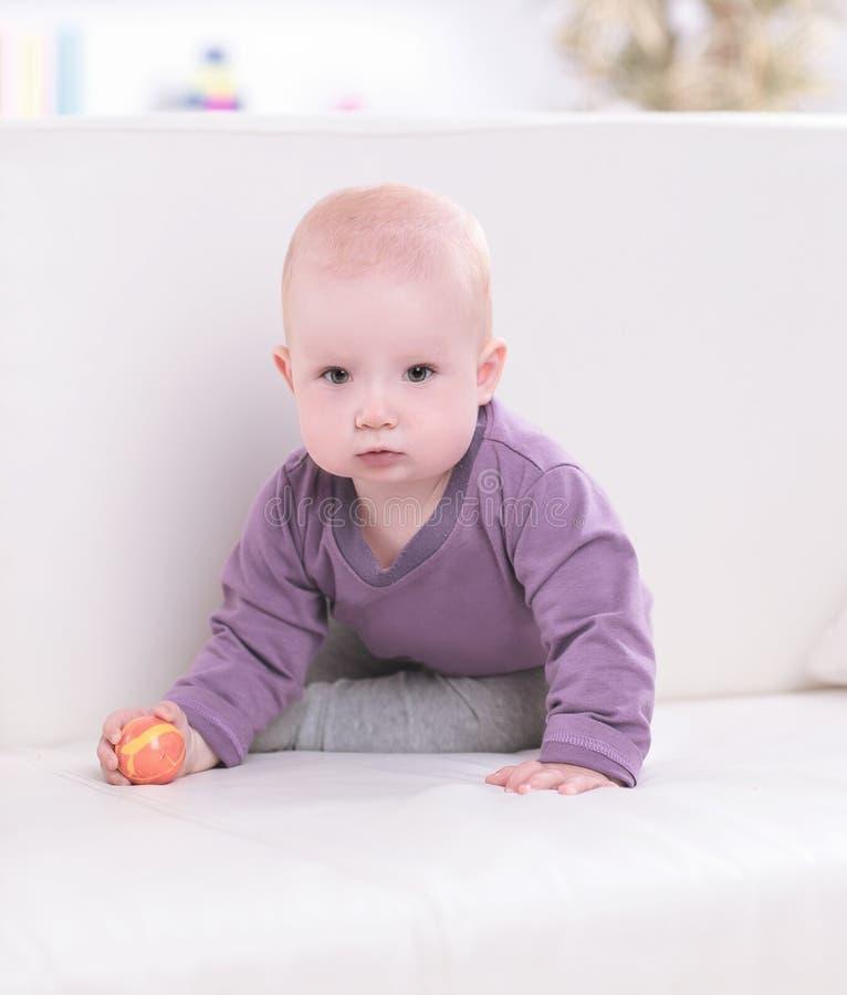 Bebê bonito que joga com uma bola no sofá imagem de stock royalty free