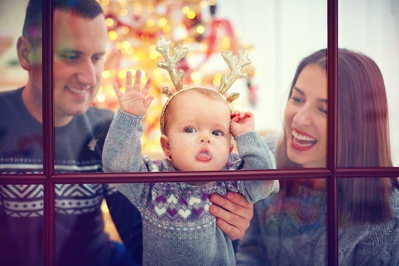Bebê bonito que lambe a janela, apreciando feriados do Natal com a família em casa imagem de stock