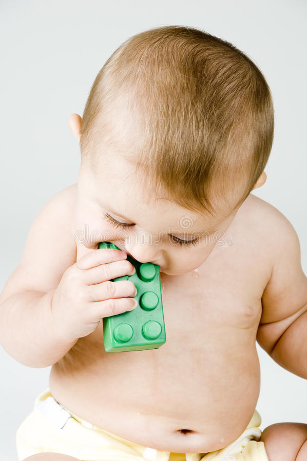 Bebê bonito que mastiga no brinquedo foto de stock royalty free