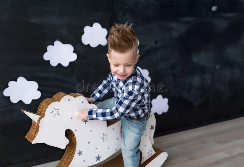 Bebê bonito que monta o brinquedo tradicional de madeira do cavalo de balanço na sala Criança que joga na sala do berçário foto de stock