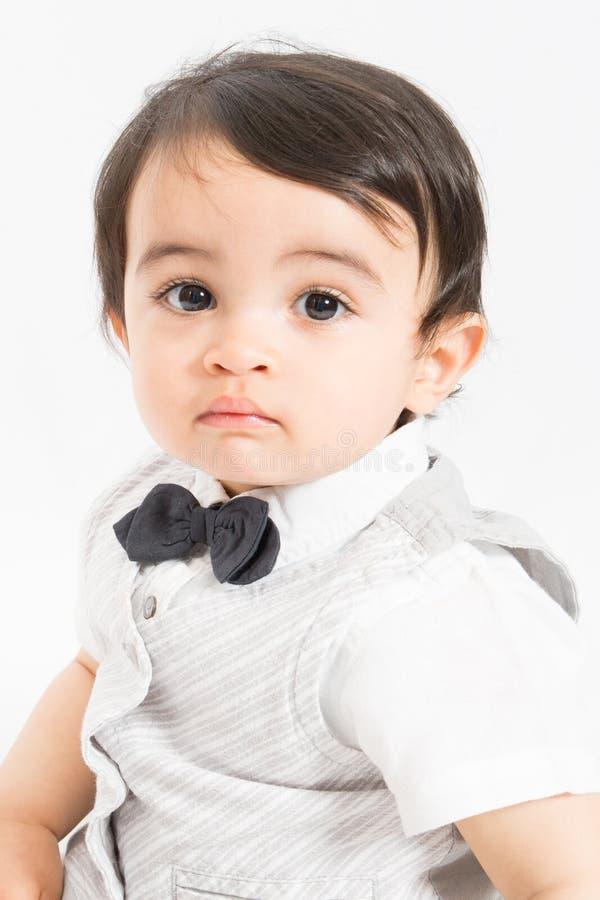 Bebê bonito que olha a câmera com seu laço vestindo da criança adorável grande dos olhos fotos de stock royalty free