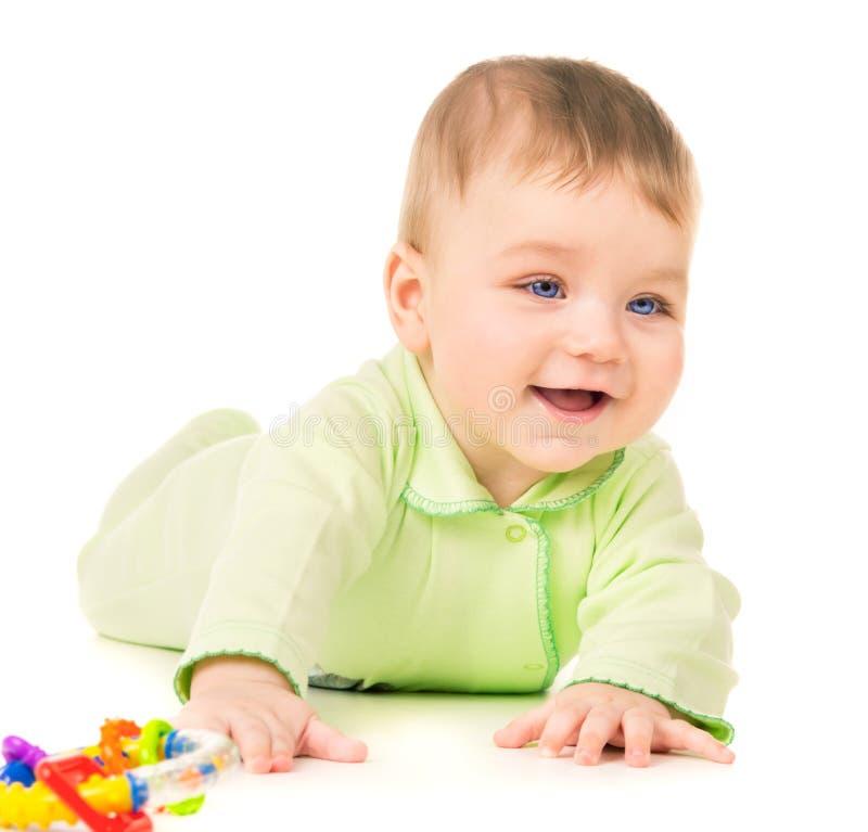 Bebê bonito que rasteja e que joga com brinquedos fotos de stock royalty free