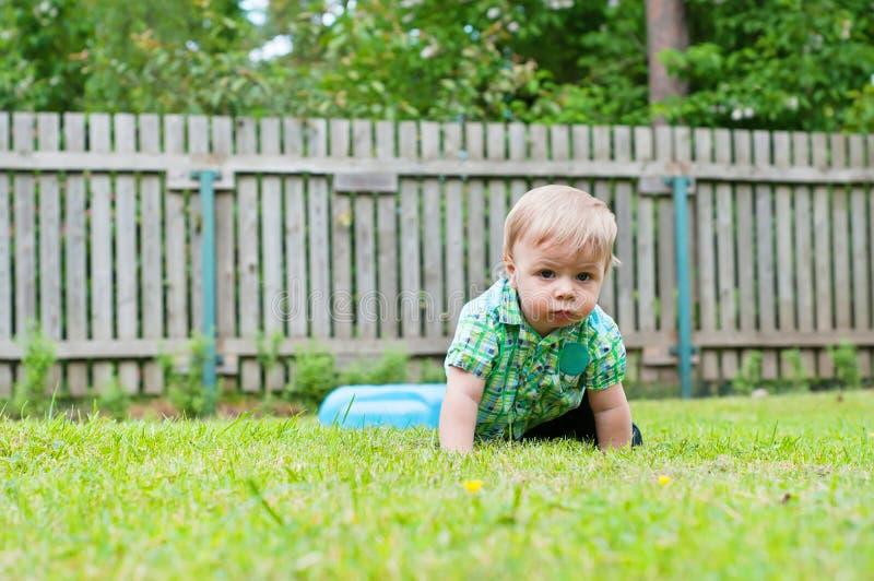 Bebê bonito que rasteja na grama imagem de stock