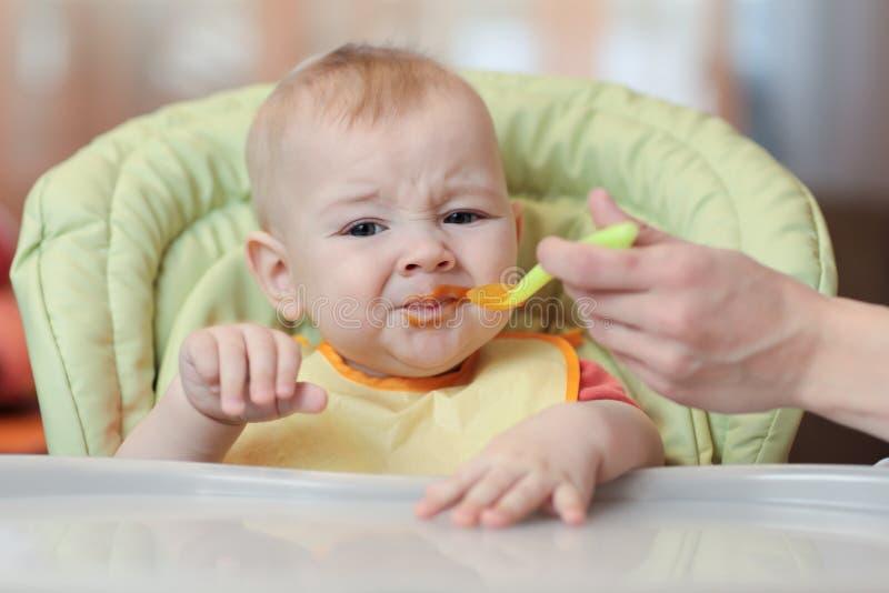 Bebê bonito que recusa comer o alimento da colher com a cara suja do puré vegetal imagens de stock royalty free