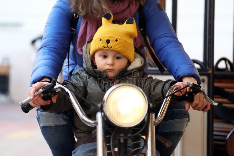 Bebê bonito que senta-se em uma motocicleta com sua mamã fotografia de stock