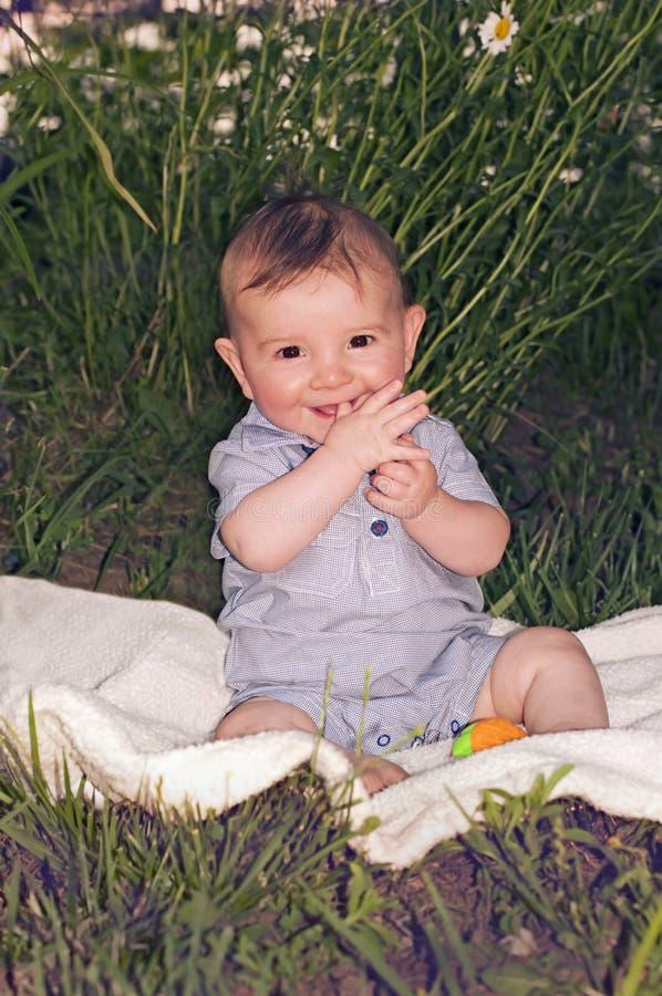 Bebê bonito que senta-se na cobertura imagem de stock