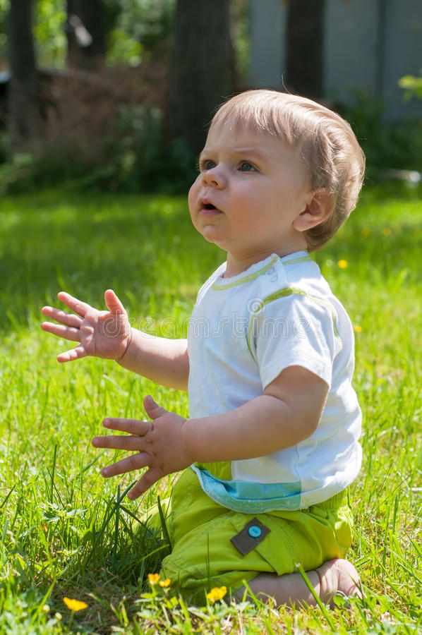 Bebê bonito que senta-se na grama imagem de stock royalty free
