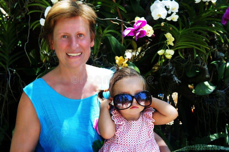 Bebê bonito que senta-se no regaço de uma mulher nas orquídeas do fundo Riso da mulher bebê que joga com óculos de sol imagem de stock royalty free