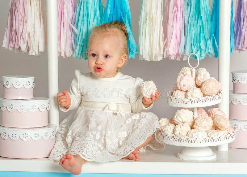 Bebê bonito que senta-se perto da casa fabulosa do marshmallow foto de stock