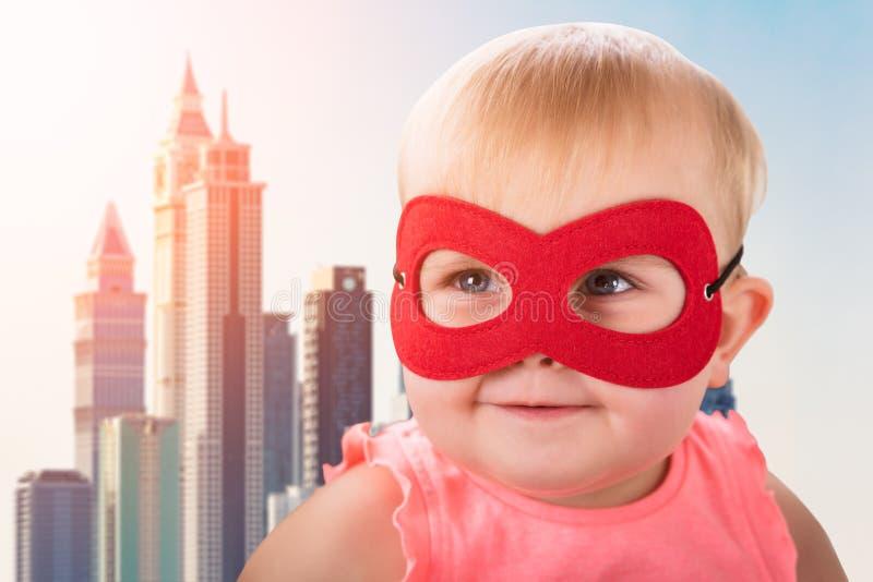 Bebê bonito que veste a máscara vermelha fotos de stock