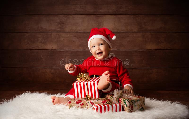 Bebê bonito Santa Claus Happy Smiling que senta-se com presentes de Natal imagens de stock