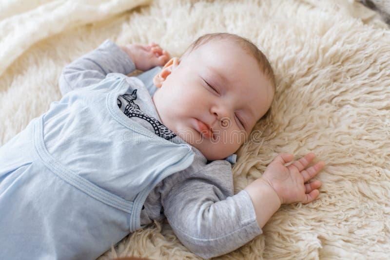 Bebê calmo que encontra-se em uma cama ao dormir em uma sala brilhante foto de stock royalty free