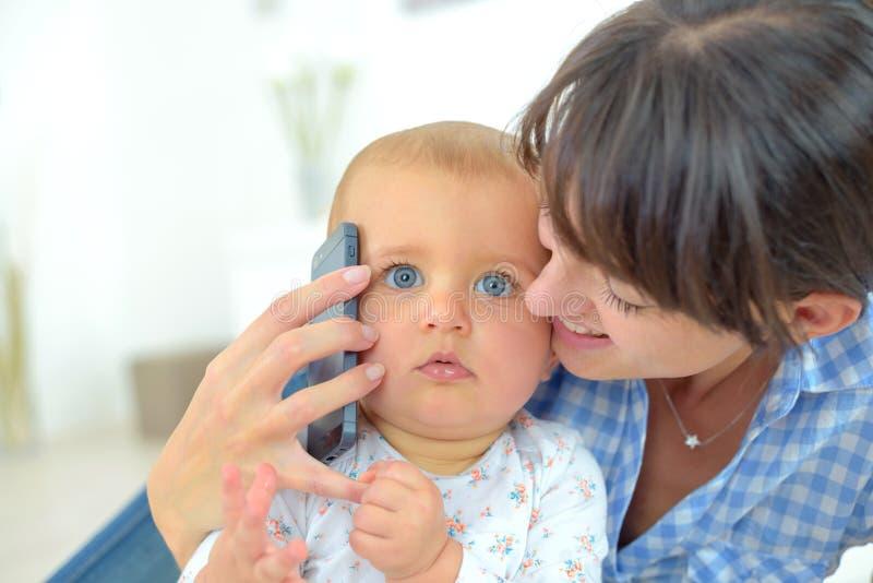 Bebê carying da mãe que fala no telefone imagens de stock