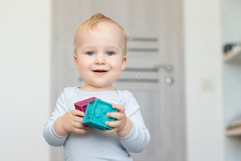 Bebê caucasiano adorável bonito que joga brinquedos coloridos em casa Criança feliz que tem a torre de construção do divertimento fotografia de stock royalty free