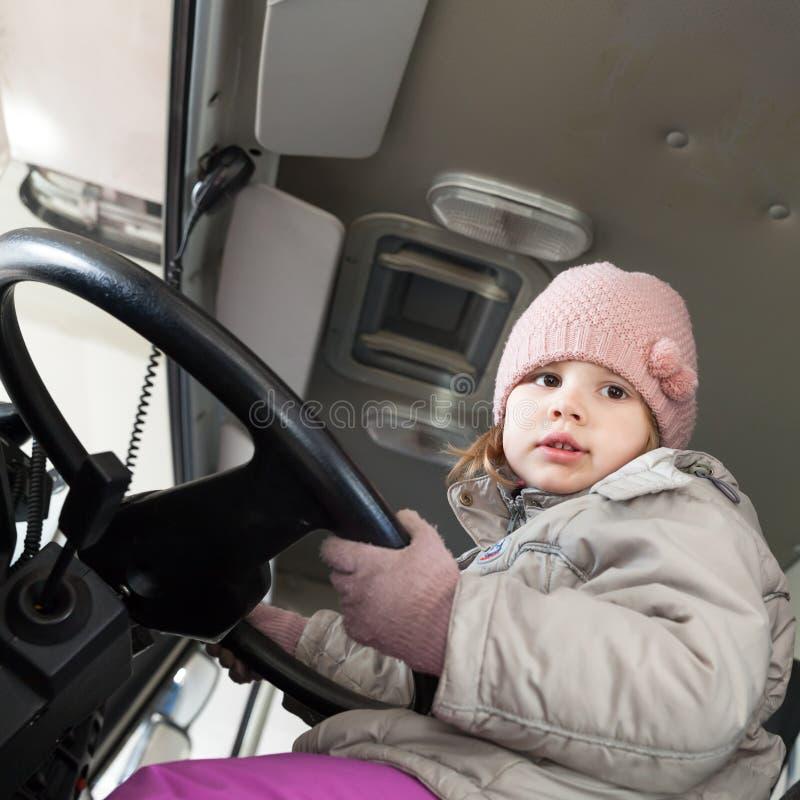 Bebê caucasiano bonito que conduz o caminhão grande da carga imagens de stock