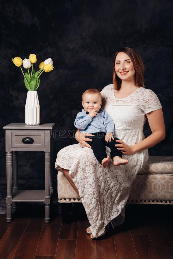 Bebê caucasiano do pai fêmea e do filho que senta-se junto no sofá dentro Feriado feliz do dia da mãe imagens de stock royalty free