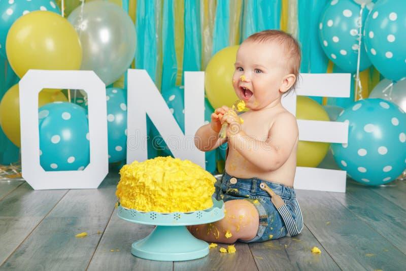 Bebê caucasiano que comemora seu primeiro aniversário Quebra do bolo imagens de stock