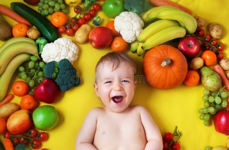 Bebê cercado com frutas e legumes imagens de stock royalty free