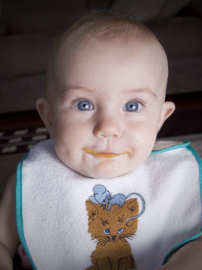 Bebê com alimento nos bordos fotografia de stock royalty free
