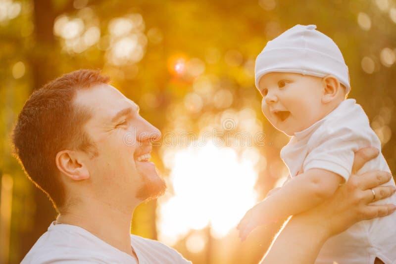 Bebê com faher no parque nos raios do por do sol Criança na natureza fora Luminoso Cena da família do verão imagens de stock royalty free