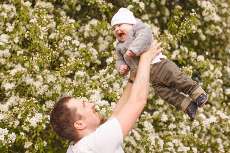 Bebê com faher no parque nos raios do por do sol Criança na natureza fora Luminoso Cena da família do verão fotografia de stock