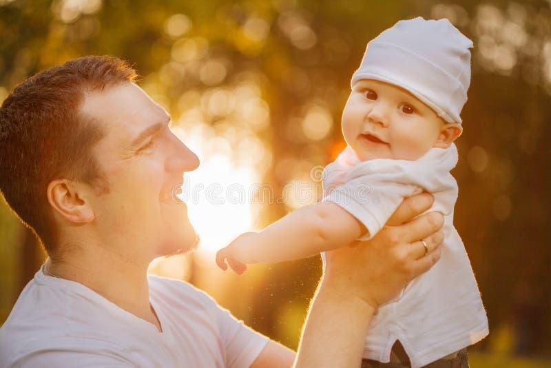 Bebê com faher no parque nos raios do por do sol Criança na natureza fora Luminoso Cena da família do verão fotografia de stock royalty free