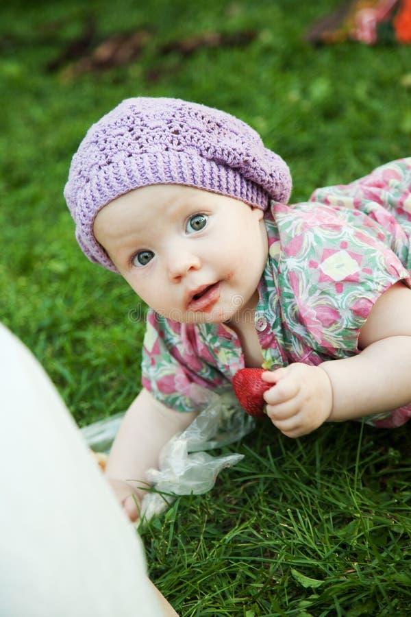 Bebê com a morango na natureza fotos de stock royalty free