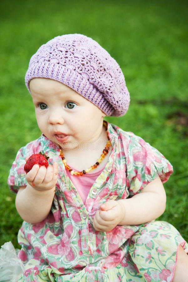 Bebê com a morango na natureza imagem de stock