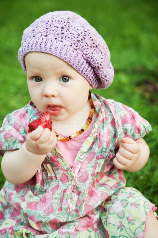 Bebê com a morango na natureza imagens de stock