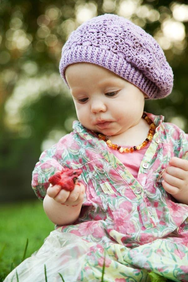 Bebê com a morango na natureza fotos de stock