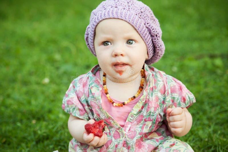 Bebê com a morango na natureza fotografia de stock