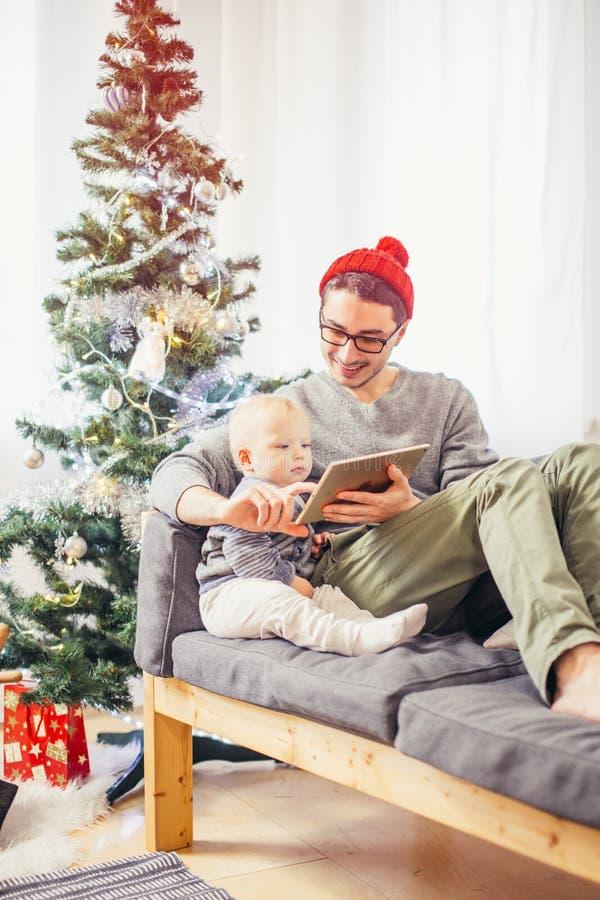 Bebê com o pai que senta e que usa a tabuleta digital durante o Natal foto de stock