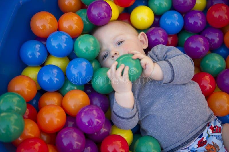 Bebê com o tecido reusável da fralda na lagoa da bola imagem de stock royalty free