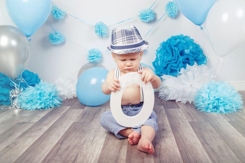 Bebê com olhos azuis com os pés descalços nas calças com os suspensórios e o chapéu, sentando-se no assoalho de madeira no estúdi imagens de stock