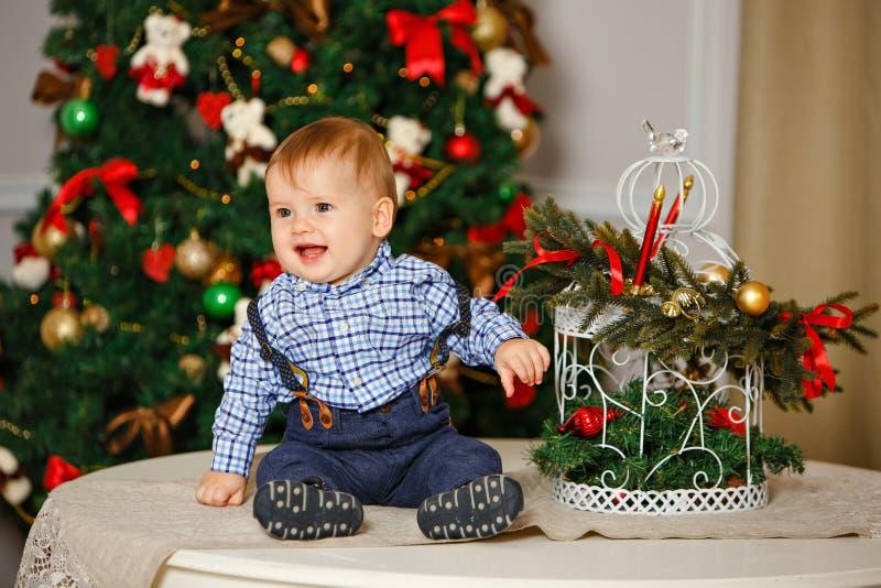 Bebê com os mordentes carnudos na camisa azul que sorri no Natal fotografia de stock royalty free