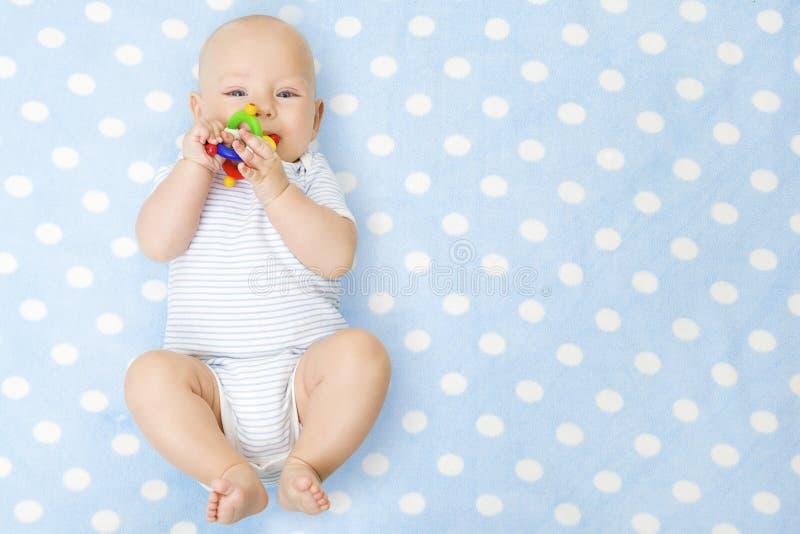 Bebê com Teether Toy In Mouth Lying sobre o fundo azul, feliz fotografia de stock