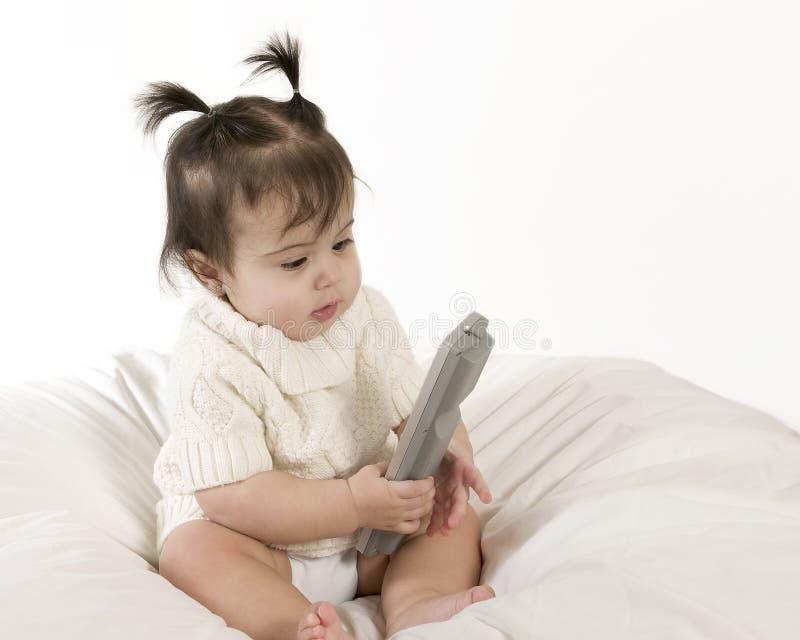 Bebê com a tevê de controle remoto imagens de stock royalty free