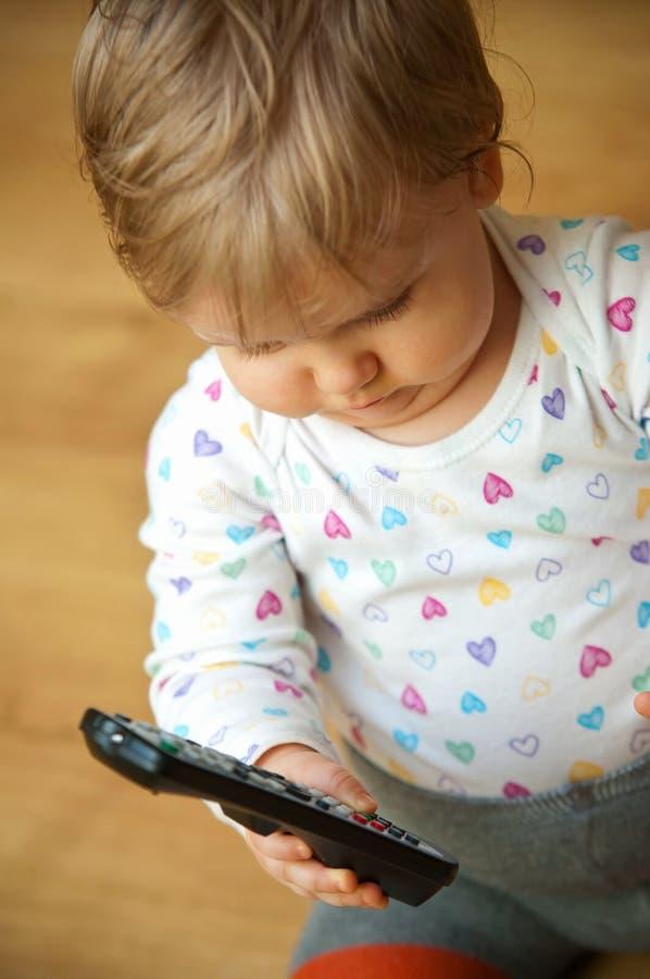Bebê com um controlo a distância da tevê fotografia de stock