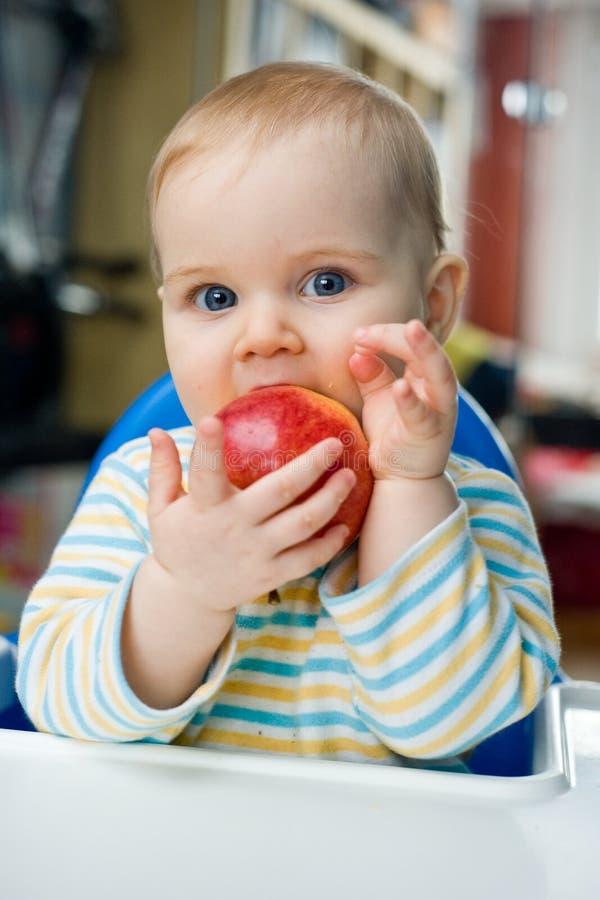 Bebê com uma maçã em casa; vertical imagem de stock