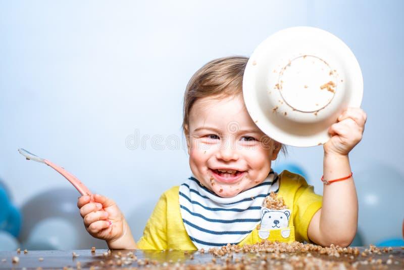 Bebê comendo, rosto engraçado de bebê com prato fotografia de stock royalty free
