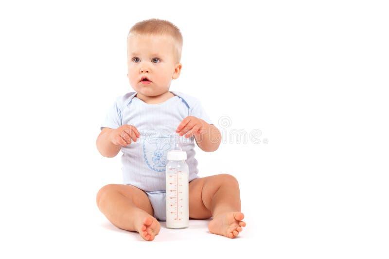 Bebê confuso bonito em pijamas azuis com leite imagens de stock royalty free
