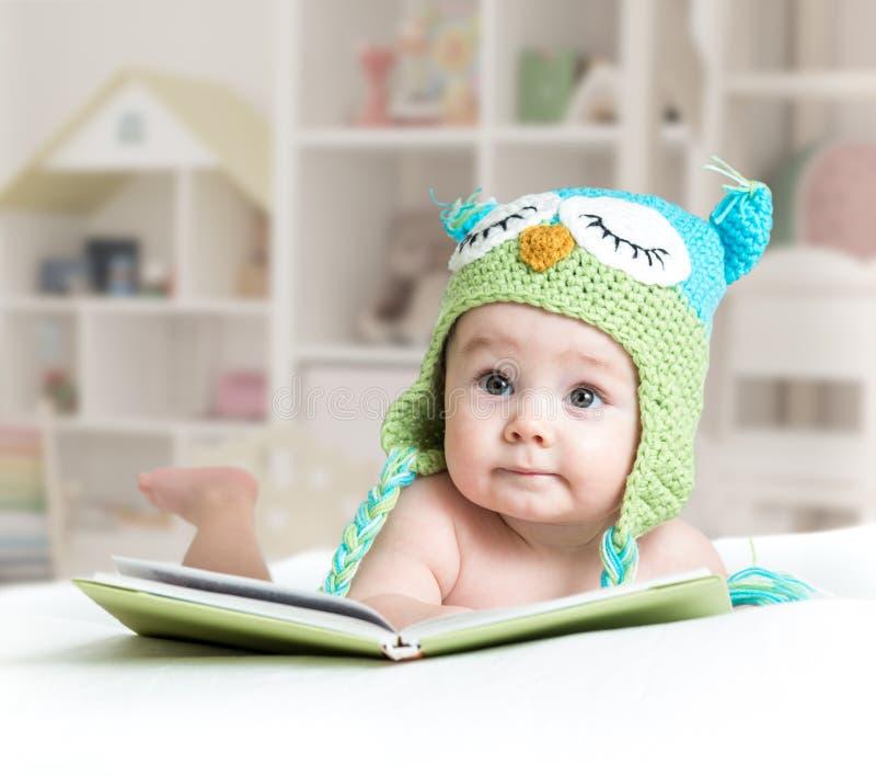 Bebê coruja engraçada na coruja feita malha do chapéu com o livro no berçário fotografia de stock royalty free