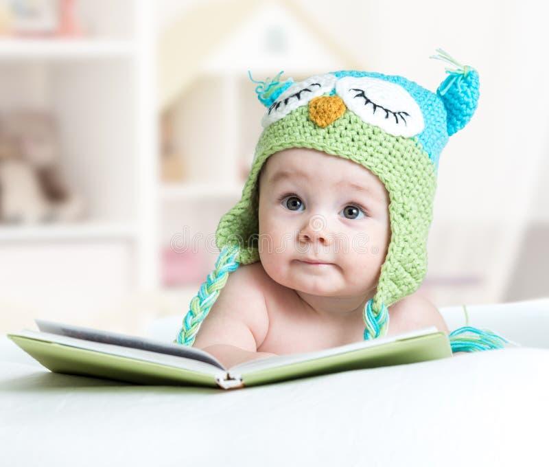 Bebê coruja engraçada na coruja feita malha do chapéu que encontra-se com o livro no berçário fotos de stock