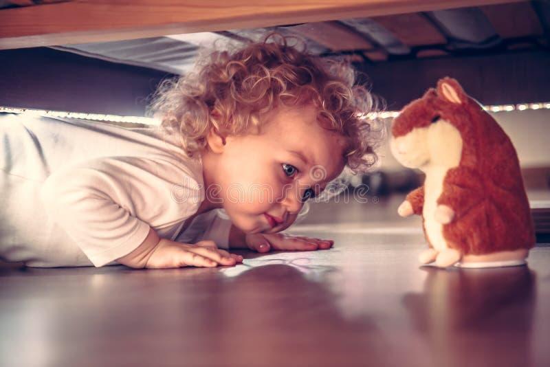 Bebê curioso bonito engraçado que joga sob a cama com o hamster do brinquedo no estilo do vintage foto de stock royalty free