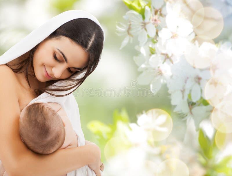 Bebê da amamentação da mãe sobre as flores de cerejeira imagens de stock royalty free
