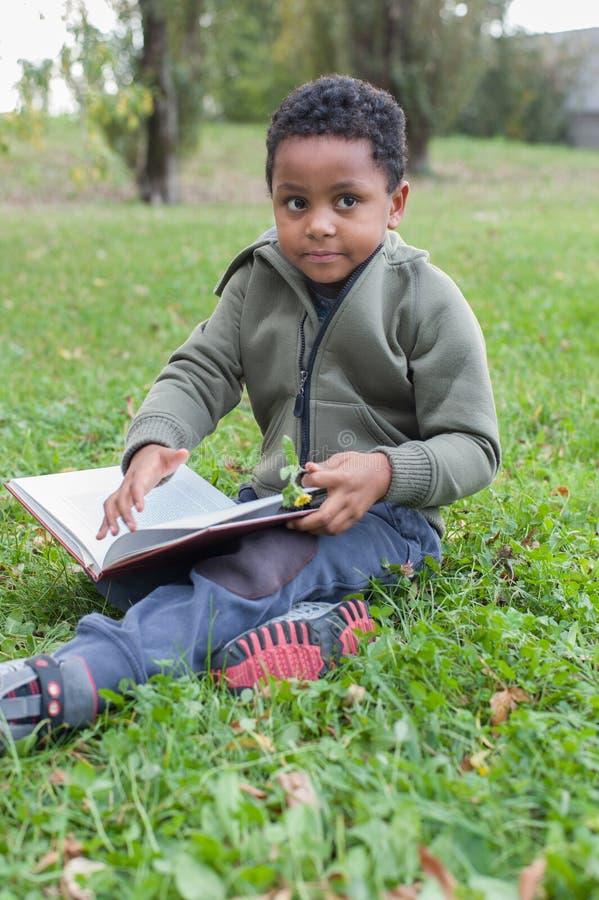 Bebê da cor que lê um livro fotografia de stock royalty free