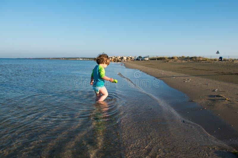 Bebê da criança que joga na água do mar rasa fotografia de stock royalty free