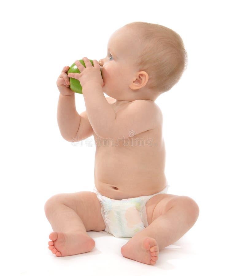 Bebê da criança que senta-se no tecido e que come a maçã verde imagem de stock royalty free