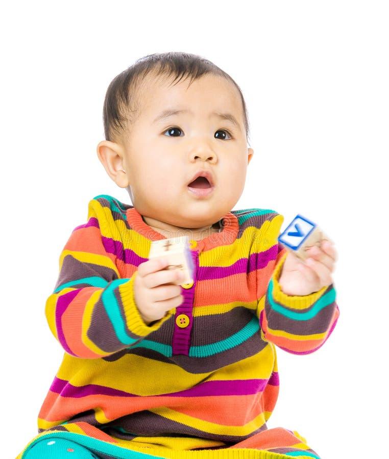 Bebê de Ásia que guarda o bloco do brinquedo imagens de stock royalty free