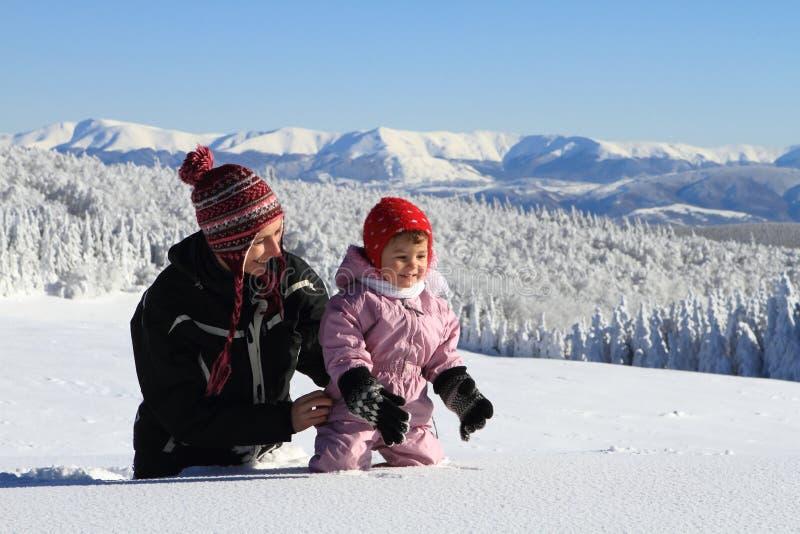 Bebê de ajuda da mamã para avançar na neve